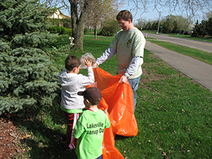 father and sons picking up trash
