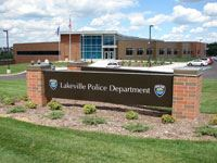 "A brick building, with a brick sign in front which reads, ""Lakeville Police Station."""